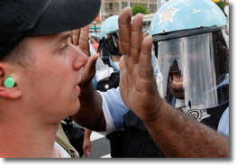 At NATO Protest, Chicago Police Officer Confronts Protester Wearing Green Ear Plugs on May 20, 2012