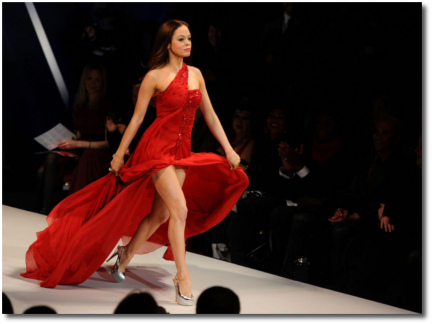 Rose McGowan on the runway in a red dress